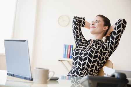 Satisfied Caucasian businesswoman relaxing in office LANG_EVOIMAGES