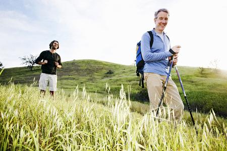 Caucasian men hiking in grass on mountain