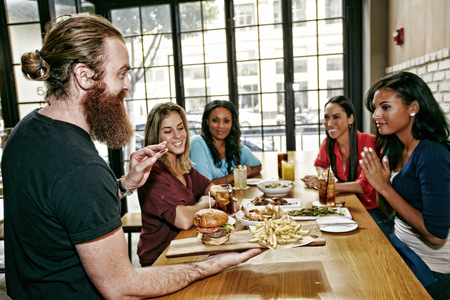 Waiter serving foods to friends at table in bar