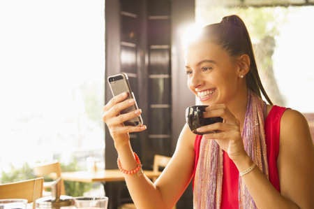 Caucasian woman posing for cell phone selfie with coffee in restaurant LANG_EVOIMAGES