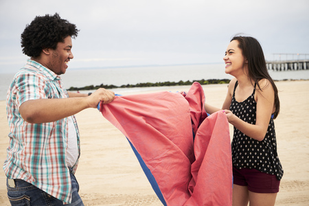 Laughing couple holding blanket on beach