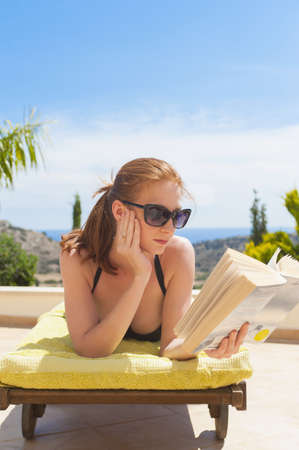 Woman laying on deck chair reading book