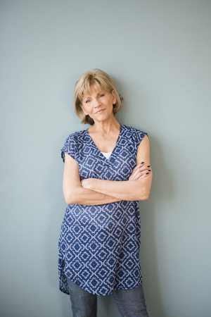 Confident older Caucasian woman standing at wall