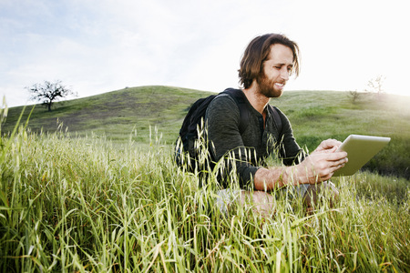 Caucasian hiker crouching in grass on mountain using digital tablet