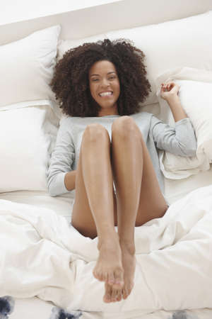 Playful Mixed Race woman laying on bed LANG_EVOIMAGES