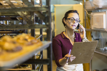 Caucasian woman holding clipboard using telephone in bakery LANG_EVOIMAGES