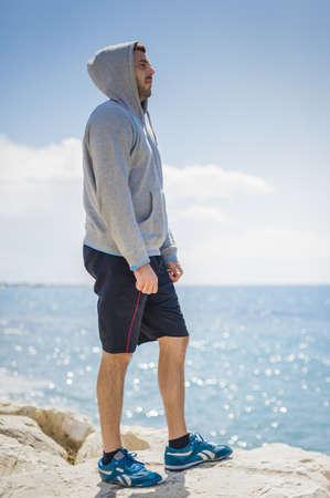 Hispanic man standing on rock near ocean LANG_EVOIMAGES