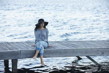 Mixed race woman sitting on dock at lake