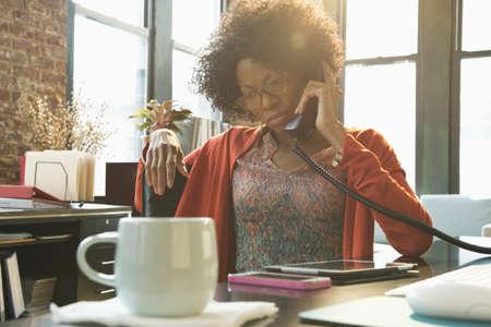 Black businesswoman talking on telephone at desk