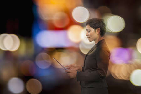 Mixed Race businesswoman using digital tablet with multicolor circles LANG_EVOIMAGES
