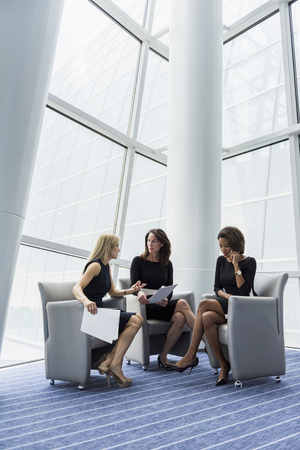 Businesswomen sitting in armchairs talking LANG_EVOIMAGES