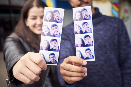 Couple showing photograph strips from photo booth LANG_EVOIMAGES