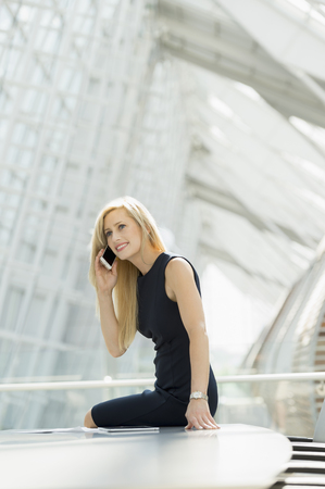 Caucasian businesswoman using cell phone in conference room