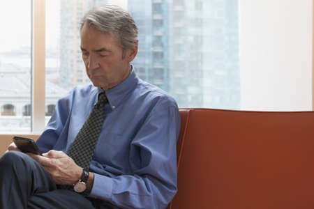 Older Caucasian businessman sitting on sofa texting on cell phone