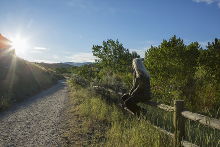 Older Caucasian woman sitting on wooden fence near mountain