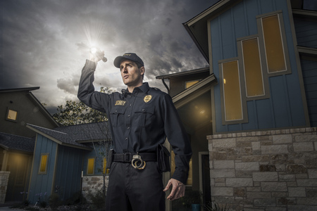 Caucasian police officer shining flashlight near house