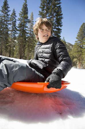 Caucasian boy sliding downhill on toboggan