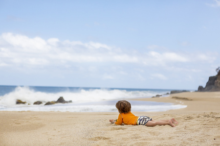 Caucasian boy laying on beach