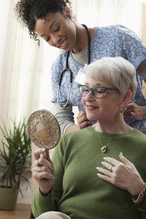 Nurse watching older woman hold mirror