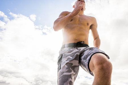 Caucasian man with bare chest running under cloudy sky LANG_EVOIMAGES