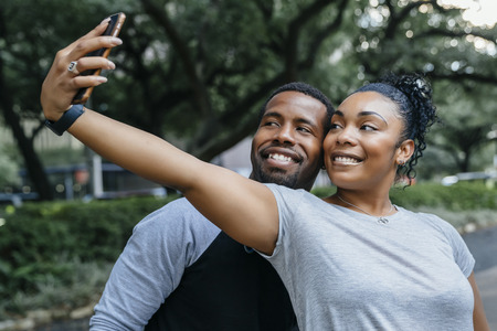Smiling Black couple posing for cell phone selfie LANG_EVOIMAGES