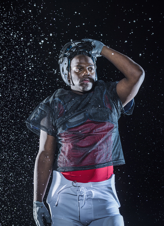 Water splashing on Black football player lifting helmet LANG_EVOIMAGES