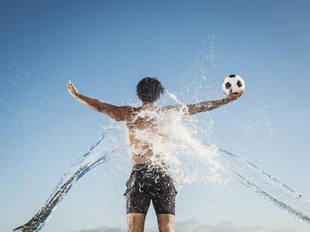 Water splashing on back of Hispanic man holding soccer ball Banco de Imagens - 102038220