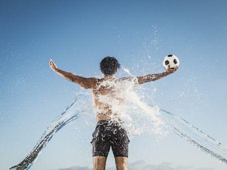 Water splashing on back of Hispanic man holding soccer ball LANG_EVOIMAGES