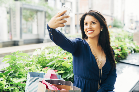 Hispanic woman sitting on bench posing for cell phone selfie LANG_EVOIMAGES