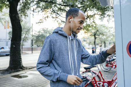 Black man with earbuds paying for bicycle rental with credit card Banco de Imagens - 102038228