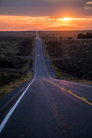 Cars driving on remote road at sunset Banco de Imagens - 102038229
