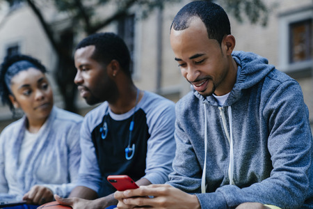 Black man texting on cell phone near friends LANG_EVOIMAGES