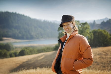 Smiling Hispanic woman wearing coat and hat outdoors