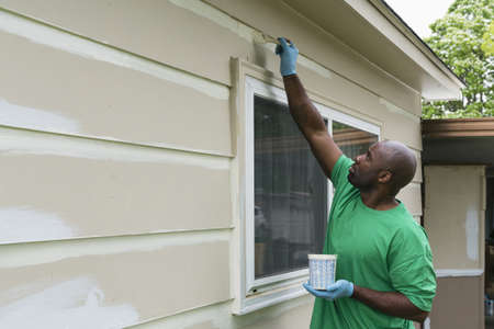 Volunteering man painting siding on house