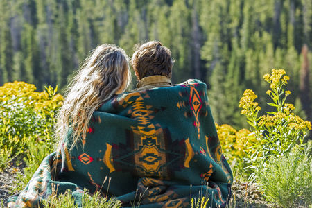Caucasian couple wrapped in blanket admiring scenic view of landscape Banco de Imagens - 102038236