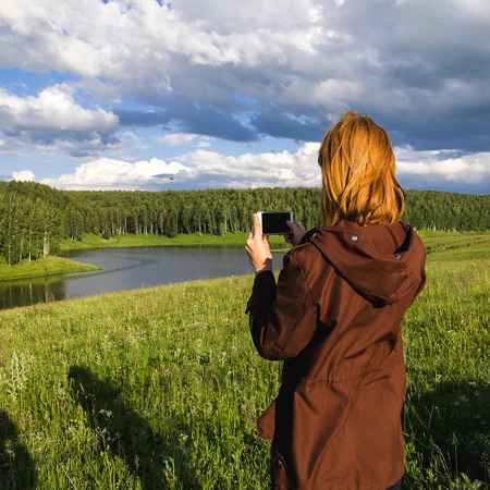 Woman photographing river with cell phone Banco de Imagens - 102038237