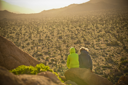 Boys sitting on rock admiring desert landscape