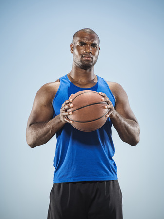 Portrait of serious Black man holding basketball