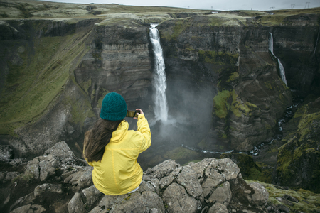Caucasian woman sitting on cliff photographing waterfall