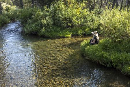 Caucasian woman sitting near tranquil river Banco de Imagens - 102038031