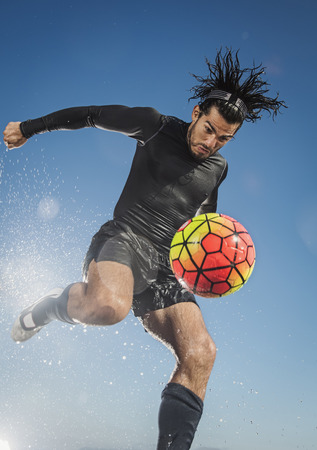 Water splashing on Hispanic man kicking soccer ball