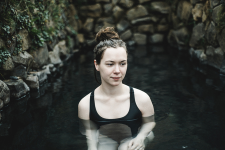 Caucasian woman swimming in pond LANG_EVOIMAGES