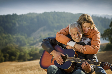 Woman hugging man playing guitar