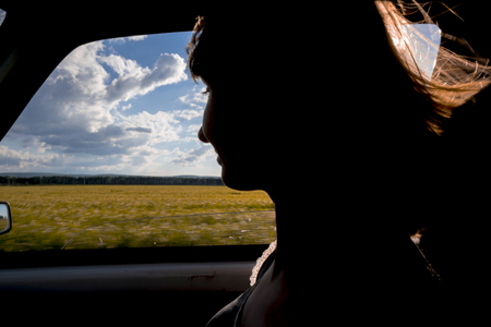 Silhouette of smiling woman passenger in car