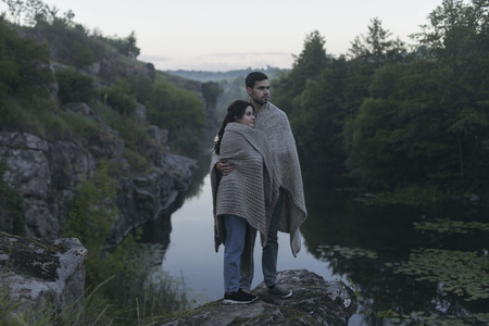 Caucasian couple wrapped in blanket standing on rock near river Banco de Imagens - 102038034
