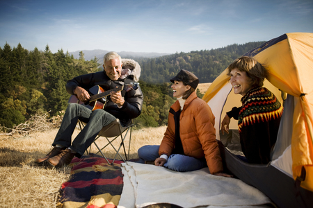 Women at camping tent listening to man playing guitar