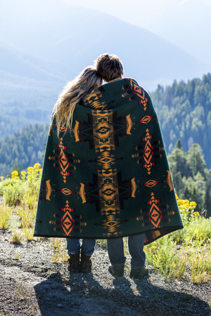 Caucasian couple wrapped in blanket admiring scenic view of landscape LANG_EVOIMAGES