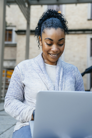 Smiling Black woman using laptop outdoors LANG_EVOIMAGES