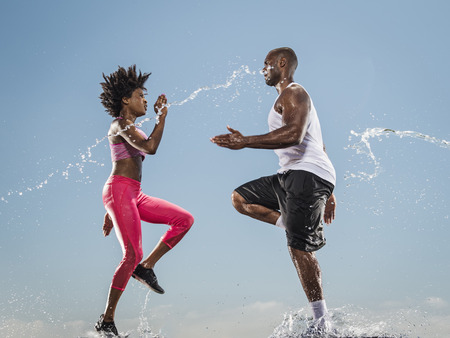 Water splashing on running Black couple