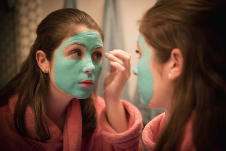 Caucasian girl applying facial mask in mirror